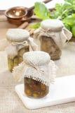 Glass jar of pickled mushrooms on jute table cloth Stock Image