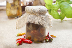 Glass jar of pickled mushrooms on jute table cloth Royalty Free Stock Photography