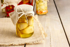 Glass jar of pickled mushrooms on wooden table Stock Photos