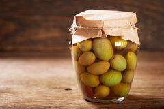 Glass jar of pickled olives stock photos
