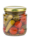 Glass jar with pickled tomatoes and cornichons stock photography