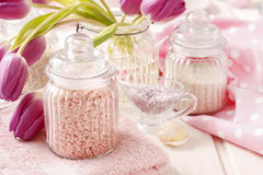 Glass jar of pink sea salt on white wooden table Royalty Free Stock Images