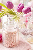 Glass jar of pink sea salt on white wooden table Stock Photography