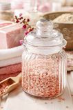 Glass jar of pink sea salt on white wooden table Stock Image