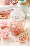 Glass jar of pink sea salt on white wooden table Royalty Free Stock Photography