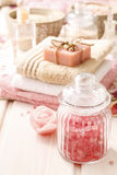 Glass jar of pink sea salt on white wooden table Stock Photo