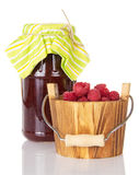 Glass jar raspberry jam and wooden bucket with berries, isolated. Stock Photo