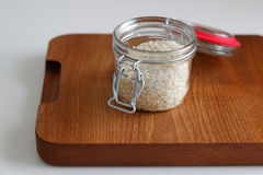 Glass Jar of Rice on Wooden Cutting Board Royalty Free Stock Image
