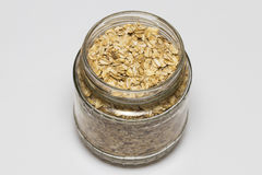 Glass jar with rolled oats isolated on white background Royalty Free Stock Photography