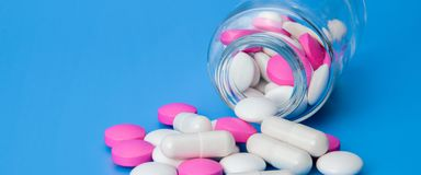 Glass jar with scattered white and pink pills on a blue background. stock image