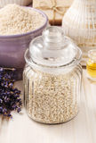 Glass jar of sea salt on white wooden table, lavender flowers Royalty Free Stock Photos