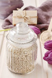 Glass jar of sea salt on white wooden table Royalty Free Stock Images