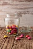 Glass jar with smarties on a wooden board Royalty Free Stock Image