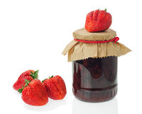Glass jar of strawberry jam with berries isolated on white backg Royalty Free Stock Images
