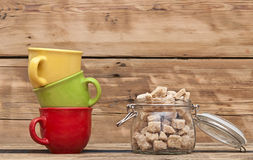 Glass jar with sugar with colorful coffee cups Royalty Free Stock Photo