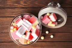 Glass jar with tasty colorful candies. On wooden background Stock Photo