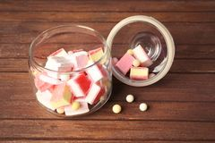 Glass jar with tasty colorful candies. On wooden background Royalty Free Stock Photo