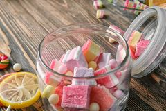 Glass jar with tasty colorful candies. On wooden background, closeup Stock Image