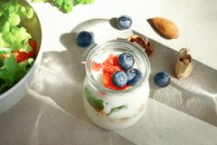 Glass jar with tasty yogurt and berries. On table Royalty Free Stock Photo