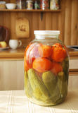 Glass jar with tinned cucumbers and tomatos Stock Photos