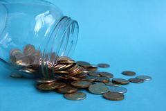 Glass jar tipped with coins on a blue background royalty free stock photo