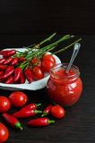 Glass jar of tomato sauce with fresh ingredients royalty free stock image