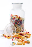 Glass jar and a variety of capsules and pills Stock Image