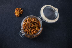 Glass jar with walnut halves Stock Photography