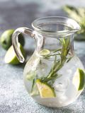 Glass jar of lime water with herbs stock image
