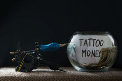 Glass jar witn money for tattoo Royalty Free Stock Photos