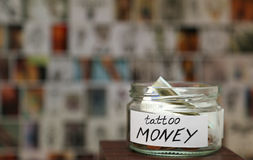 Glass jar witn money for tattoo, sketches at background Royalty Free Stock Images