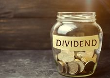 Glass jar with the word Dividend. A dividend is a payment made by a corporation to its shareholders as a distribution of profits. stock photography