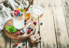 Glass jar of yogurt with berries, mint and honey Stock Image