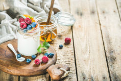 Glass jar of yogurt with fresh berries, mint and honey Stock Images