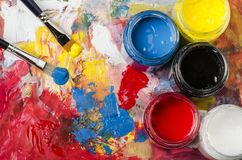 Palette with acrylic primary colors. Glass jars with acrylic primary colors and a dirty palette with a spatula and brushes royalty free stock photos