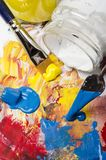 Palette with acrylic primary colors. Glass jars with acrylic primary colors and a dirty palette with a spatula and brushes stock photos