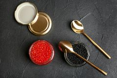 Glass jars with black and red caviar. On grey background Royalty Free Stock Photo