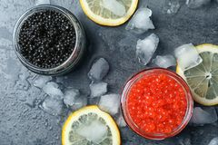 Glass jars with black and red caviar. On grey background Stock Photography
