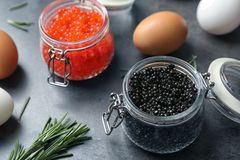 Glass jars with black and red caviar. On grey background Royalty Free Stock Image