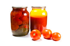 Glass jars of canned tomatoes and tomatoes juice on white backgr Royalty Free Stock Images