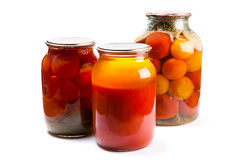 Glass jars of canned tomatoes and tomatoes juice on white backgr Royalty Free Stock Image