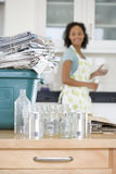 Glass jars and cans by recycling bin with newspapers in kitchen, woman in background Royalty Free Stock Image