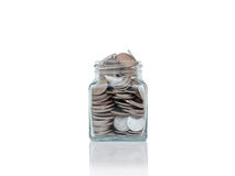 Glass jars with coins on reflective surface isolated on white. Stock Image