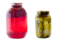 Glass jars with compote and cucumbers. Glass jars with red compote and cucumbers on white background stock photography