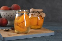 Glass jars with conserved peach halves. On wooden board royalty free stock photo
