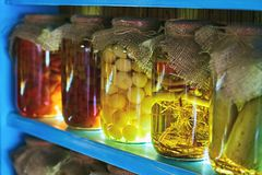 Glass jars covered with burlap fabric with different homemade canned food, preserved vegetables on wooden shelves royalty free stock photos