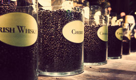 Glass jars with different flavour coffee on display. Coffee background with vintage colour feeling Stock Images