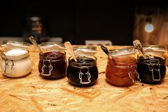 Glass jars with different kinds of jam and berries on wooden table stock image