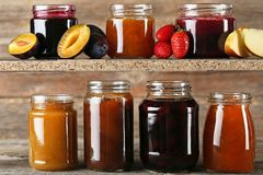 Different kinds of jam. Glass jars with different kinds of jam on wooden table Royalty Free Stock Images