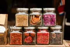 Glass jars with dry fruits and spices on a wooden table. Glass jars with dry fruits and spices on a wooden table in a cafe Stock Photography